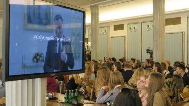 """Uczestnicy spotkania podczas przemówienia Prezydenta. Na ekranie Andrzej Duda i podpis """"Cały czas się czegoś uczę"""""""