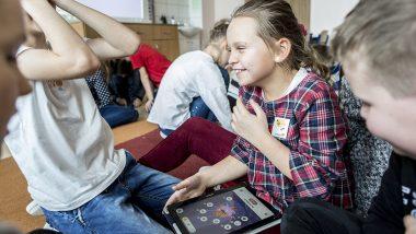 Dzieci siedzą na podłodze w sali szkolnej. Dziewczynka na pierwszy planie trzyma na kolanach tablet.